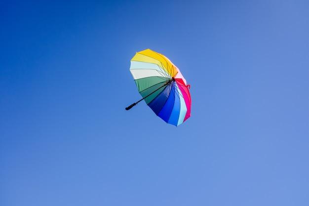 Mehrfarbiger regenschirm, der über hellblauem himmelhintergrund hängt