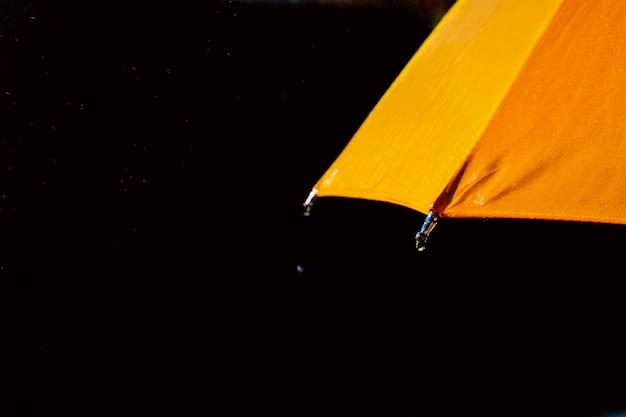 Mehrfarbiger regenschirm unter regentropfen isoliert auf schwarz