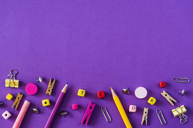 Mehrfarbiger schulbedarf auf violettem hintergrund mit kopienraum.