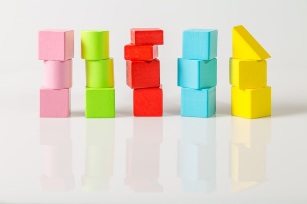 Mehrfarbiger würfel aus geometrischen holzformen isoliert auf einem weiß
