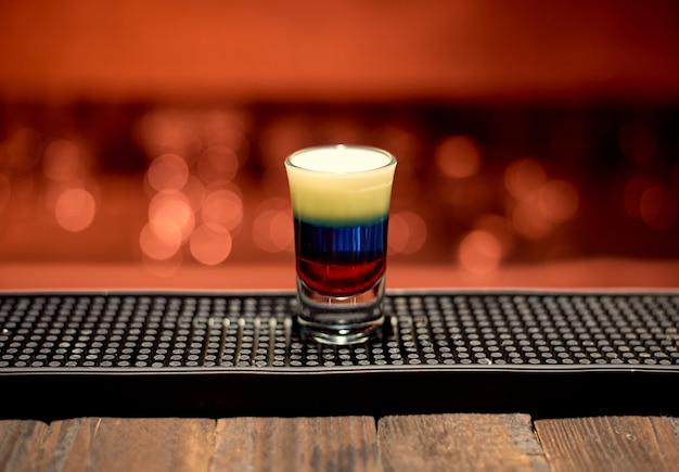 Mehrfarbiges alkoholisches getränk in einer bar auf einem hellen hintergrund