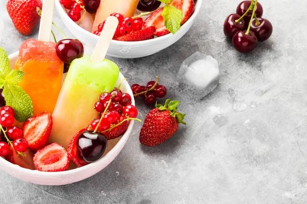 Mehrfarbiges eis am stiel mit erdbeere, roter johannisbeere und kirsche