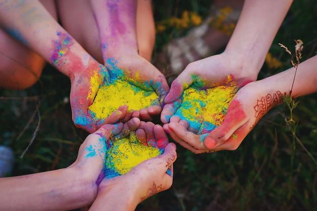 Mehrfarbiges farbpulver in den händen beim holly festival. regenbogen.