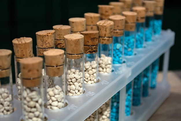 Mehrfarbiges granulat aus mikronährstoffdünger in reagenzgläsern hintereinander