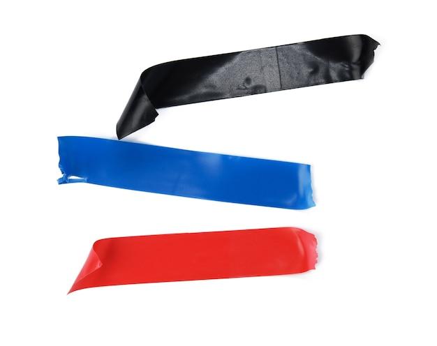 Mehrfarbiges gummi-isolierband, stücke isoliert auf weißem hintergrund, nahaufnahme