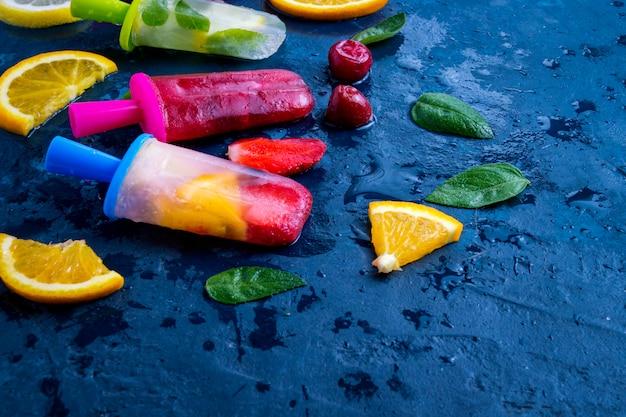 Mehrfarbiges helles frucht-eis am stiel mit erdbeer-, kirsch-, zitronen-, orangen-, zitronen- und minzaroma und frischen früchten auf einer dunkelblauen oberfläche