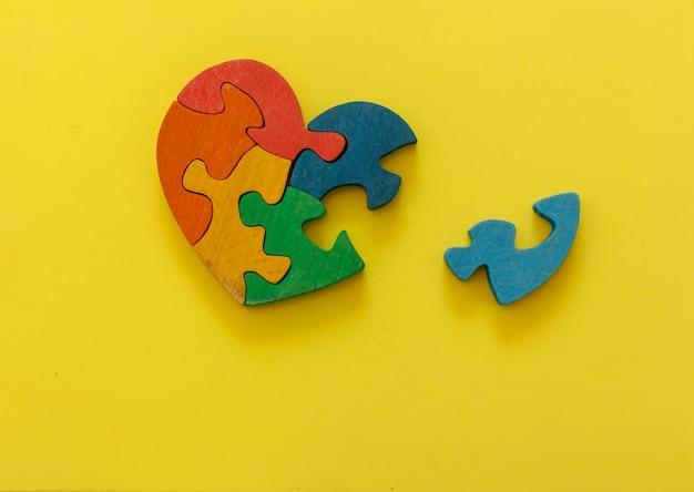 Mehrfarbiges holzpuzzle in form eines herzens auf gelbem hintergrund. konzept valentinstag, beziehung. platz für text