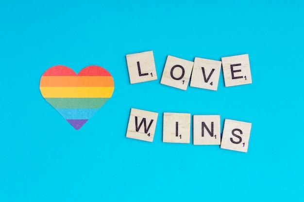 Mehrfarbiges lgbt-herz mit liebe gewinnt motto auf blauem hintergrund
