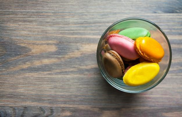 Mehrfarbiges makkaroni des französischen nachtischs auf einem braunen holztisch