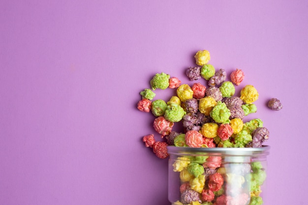 Mehrfarbiges popcorn mit fruchtgeschmack in glasbechern auf pink