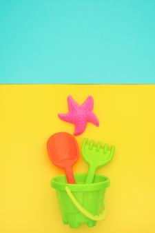 Mehrfarbiges set kinderspielzeug für sommerspiele im sandkasten oder am sandstrand auf blau und gelb