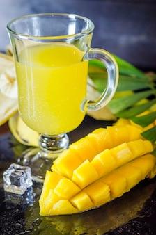 Mehrfruchtsaft mit früchten auf schwarzem hintergrund mit tropischen blättern