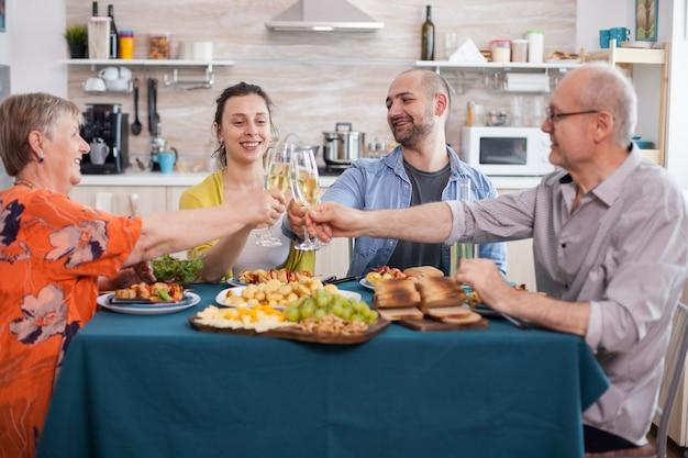 Mehrgenerationen-familie, die während des mittagessens mit weißwein anstößt. leckere gewürzte kartoffeln. ältere eltern. leckere trauben.