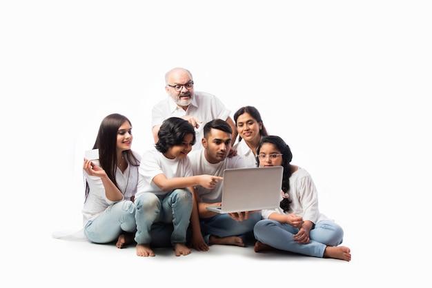 Mehrgenerationen-indische asiatische familie von sechs online-shopping mit laptop und elektronischer karte beim sitzen vor weißem hintergrund