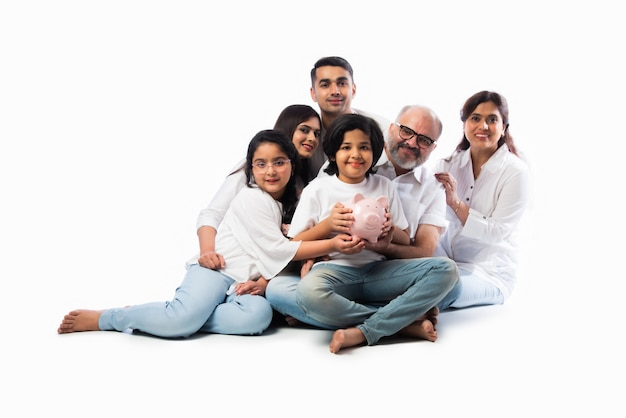 Mehrgenerationen-indische sechsköpfige familie, die ein sparschwein hält, während sie weiße tücher trägt und gegen eine weiße wand steht