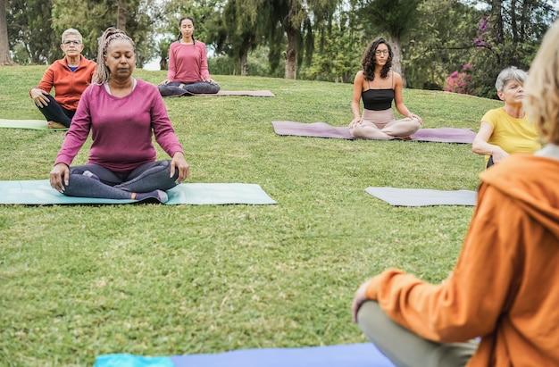 Mehrgenerationen-leute, die yoga-kurse im stadtpark machen - konzentrieren sie sich auf das linke gesicht der älteren frau