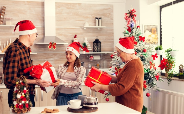 Mehrgenerationenfamilie feiert weihnachten mit geschenkboxen