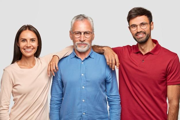 Mehrgenerationenkonzept. das familienporträt des reifen zerknitterten mannes, gekleidet im stilvollen hemd, steht zwischen seiner tochter und seinem sohn