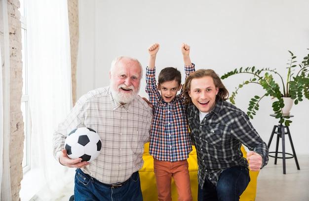 Mehrgenerationenmänner, die fernsehen, stützen fußballteam