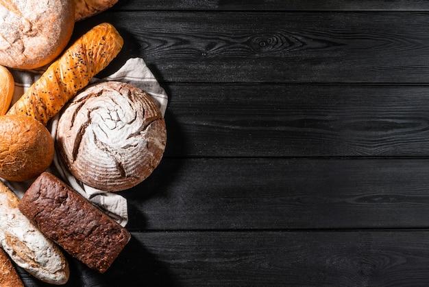 Mehrkorn-brotbrot-bäckerei auf stoffholztisch und dunklem hintergrund