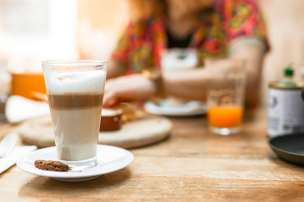 Mehrschichtiges kaffeeglas mit plätzchen auf untertasse