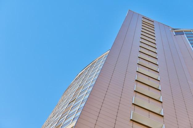 Mehrstöckige gebäudefassade, kopierraum. rhythmus in der fotografie. neue mehrstöckige fassade, fenster und wohnblock, nahaufnahme. moderne wohnungen in hochhaus