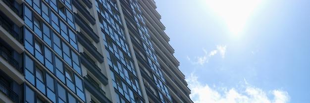 Mehrstöckiges gebäude mit vielen glasfenstern, die vor dem hintergrund des blauen himmels und der sonne stehen