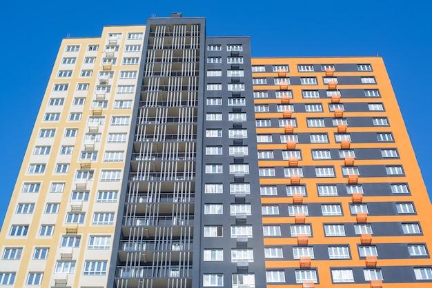 Mehrstöckiges wohngebäude im außenbereich. mietshaus, ansicht von unten. mehrfarbiges modernes gebäude gegen den blauen himmel während des tages.