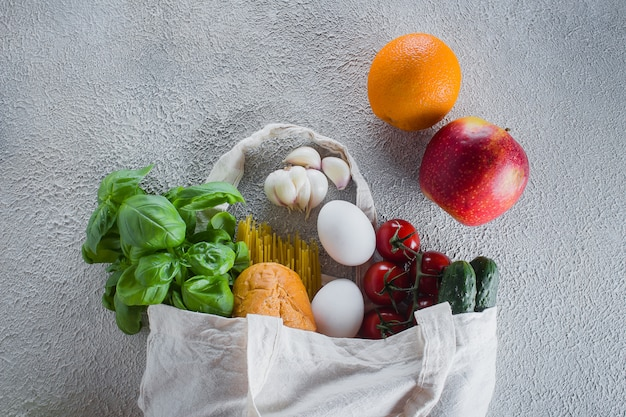 Mehrwegbeutel mit lebensmitteln. einkaufstasche, minimaler abfall. basilikum, tomatenkirsche, knoblauch in stoffbeutel