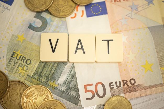 Mehrwertsteuer konzept. mehrwertsteuerwort auf euro-geldbanknoten auf dem desktop. geschäftliches und wirtschaftliches hintergrundfoto
