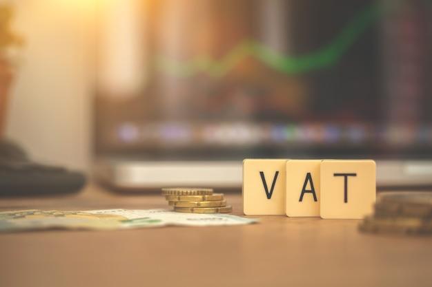 Mehrwertsteuer-konzept. wort-mehrwertsteuer und münzen auf börsen- oder devisenhandelsdiagrammen und kerzenhintergrund. geschäfts- und investitionsfoto