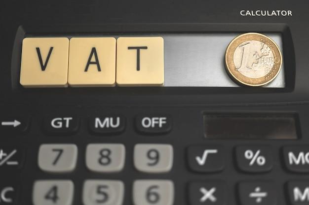 Mehrwertsteuer umsatzsteuer-, finanz- und betriebswirtschaftliche hintergrund. taschenrechner und mehrwertsteuertext auf holzwürfelblöcken