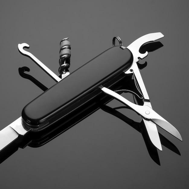 Mehrzweck-klappmesser auf schwarzem hintergrund. schweizer taschenmesser