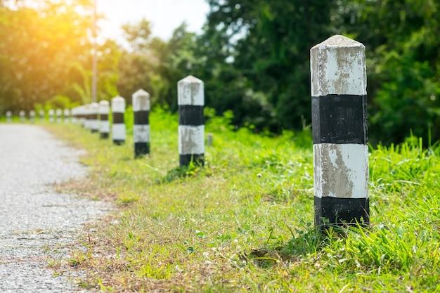 Meilensteine - schwarz-weiß-meilensteine mit grünem gras am straßenrand. konzept für den nächsten schritt.