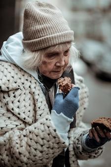 Mein abendessen. traurige obdachlose frau, die brot in der hand hält, während sie es essen will