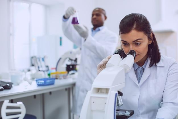 Mein arbeitsplatz. entschlossener professioneller biologe, der eine uniform trägt und in das mikroskop schaut