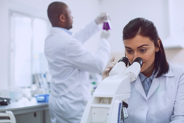 Mein arbeitstag. erfahrener professioneller biologe, der eine uniform trägt und in das mikroskop schaut