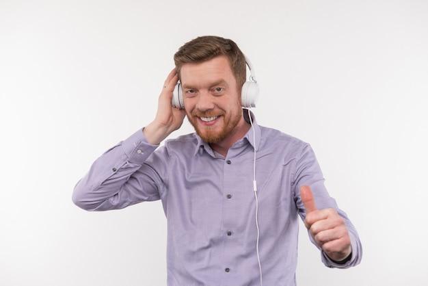 Mein favorit. glücklicher gutaussehender mann, der das ok-zeichen zeigt, während er das lied genießt