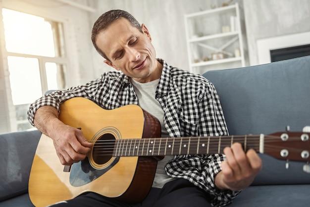 Mein hobby. gut aussehender, gut gebauter mann, der lächelt und gitarre spielt, während er auf der couch sitzt