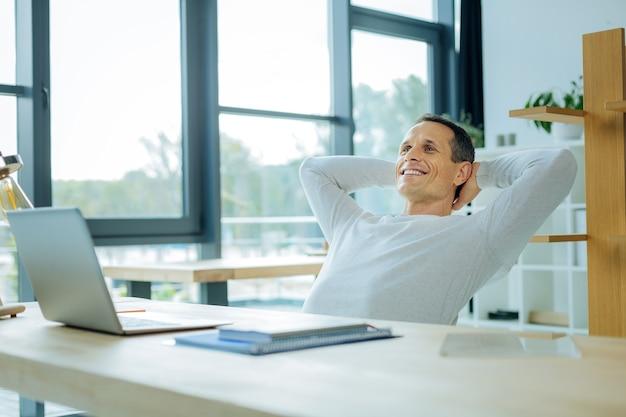 Mein job ist erledigt. erfreuter glücklicher positiver mann, der bei der arbeit lächelt und sich entspannt, während er sein projekt beendet
