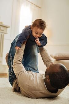 Mein leben. dunkelhaariger bärtiger afroamerikanischer mann, der mit seinem süßen kleinen sohn spielt, während er auf dem boden liegt und das kind in seinen armen hält