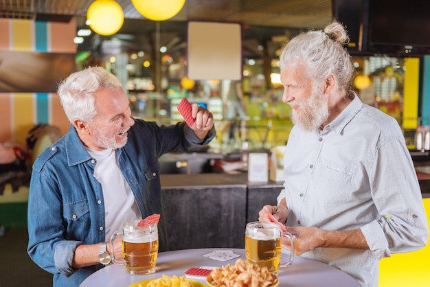 Mein sieg. positiver älterer mann, der eine karte auf den tisch legt, während er das spiel gewinnt