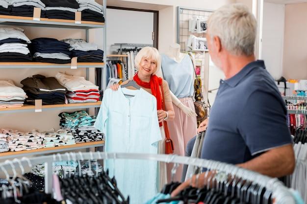 Mein stil. freudige modische ältere frau, die stilvolles kleid in den händen hält, während sie es dem verkäufer zeigt und entzückende gefühle ausdrückt