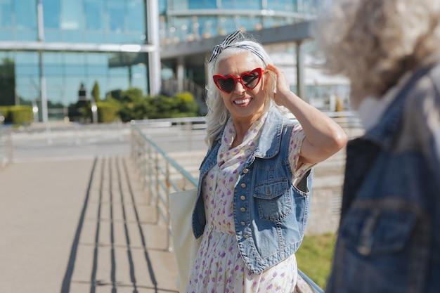 Mein stil. glückliche nette frau, die sonnenbrille trägt, während sie ihren ehemann ansieht