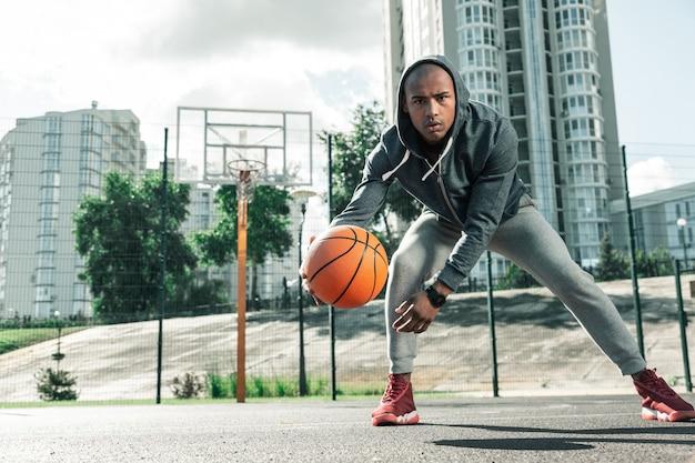 Mein training. hübscher netter mann, der basketball allein spielt, während er seine fähigkeiten verbessert