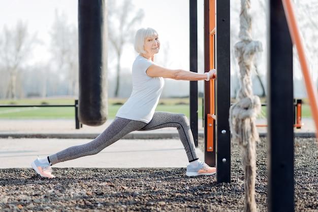 Mein training. inspirierte blonde frau, die sportkleidung trägt und im freien trainiert