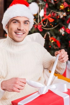 Mein weihnachtsgeschenk. hübscher junger mann mit weihnachtsmütze öffnet geschenkbox und lächelt mit weihnachtsbaum im hintergrund
