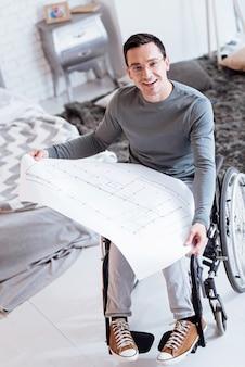 Mein zimmer. fröhlicher ungültiger ingenieur, der ein lächeln auf seinem gesicht behält und den kopf hebt, während er einen großen zug hält