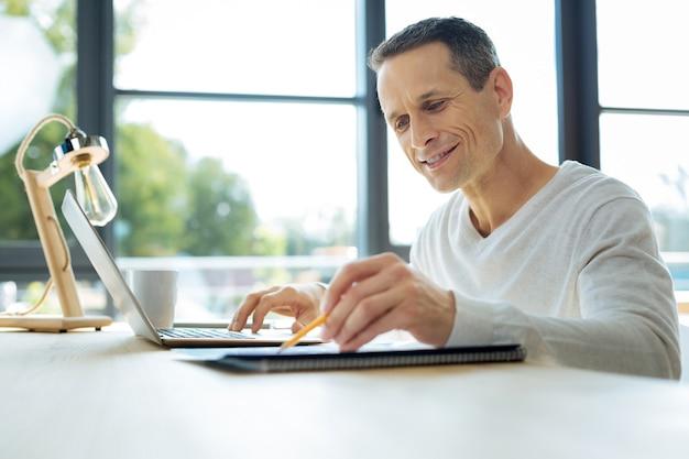 Meine arbeit. erfreut über einen positiven, gutaussehenden geschäftsmann, der vor dem laptop sitzt und den ordner mit dokumenten betrachtet, während er statistische daten vergleicht