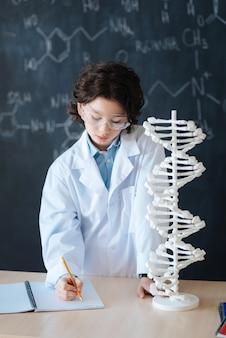 Meine aufgabe richtig machen. beteiligter nachdenklicher kleiner junge, der im labor steht und das genetische codemodell erforscht, während er mikrobiologie studiert und notizen macht